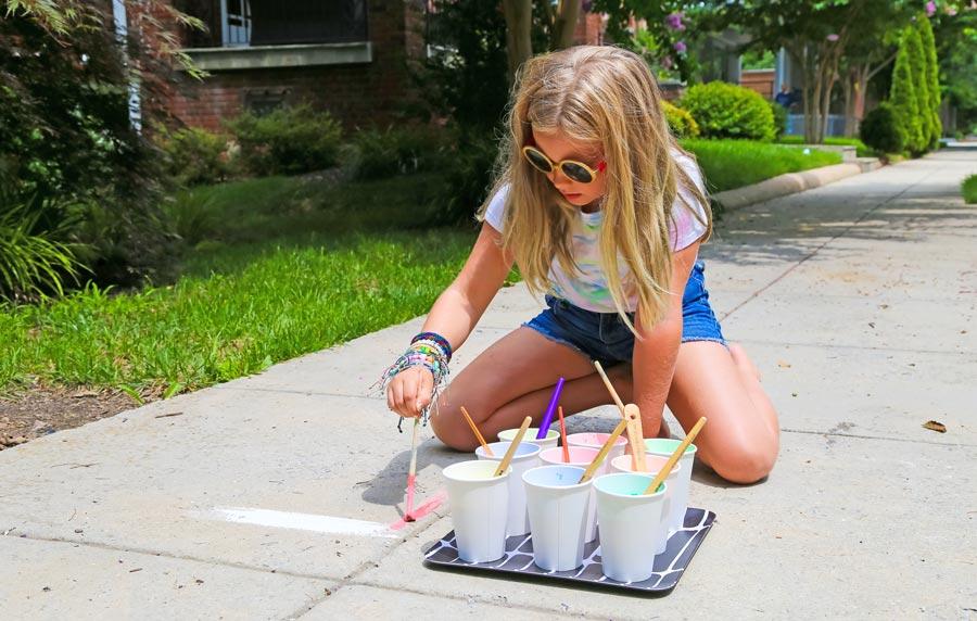 Girl painting on sidewalk with homemade sidewalk chalk paints