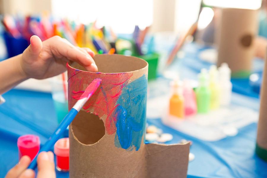 Kid decorating a cardboard tube for a DIY bug hotel craft