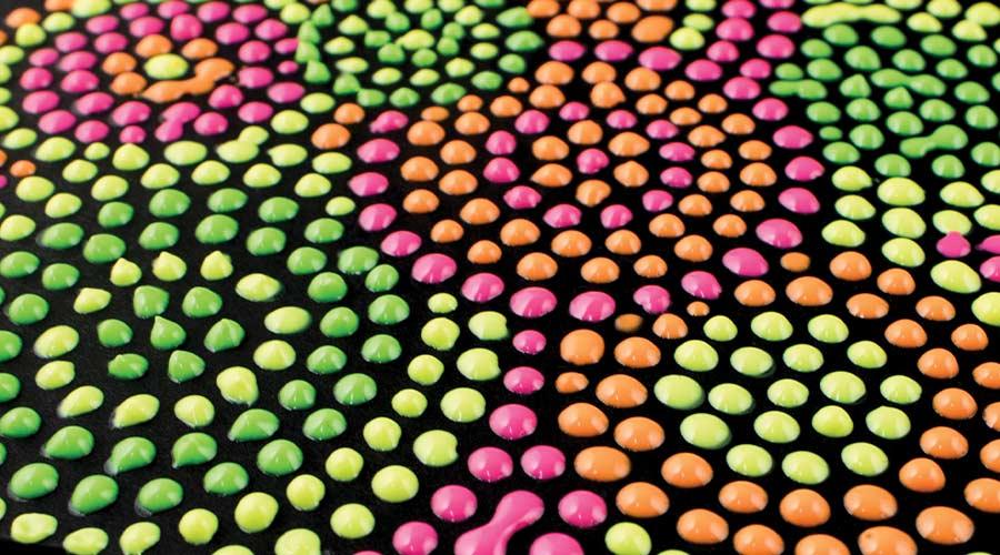 neon dots on black paper