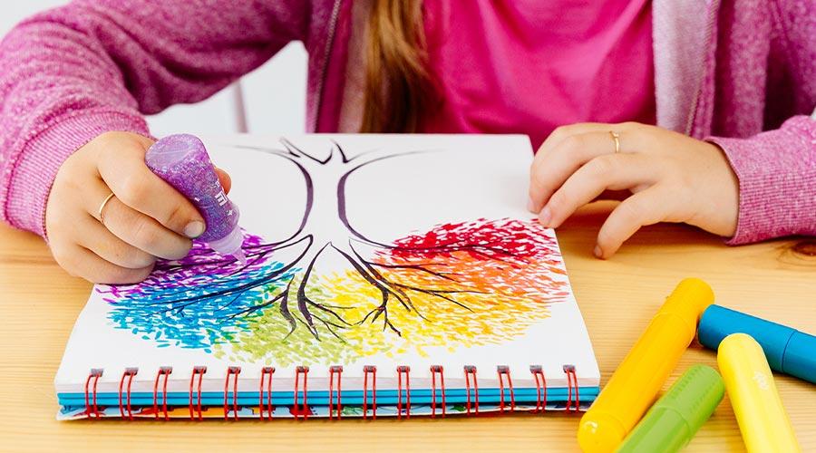 child sitting at table creating rainbow tree with purple glitter glue