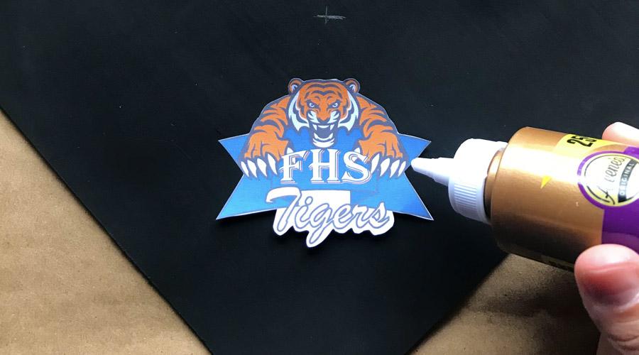 graduation cap with hand gluing on high school logo